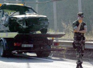 An unidentified US soldier (MA3 Patrick) walks in front of the burned car belonging to three U.S Navy sailors who were killed in a car crash in Naples, Italy, early Saturday, June 12, 2004. The vehicle flipped over on the road and burst into flames. The cause of the accident was not immediately clear.
